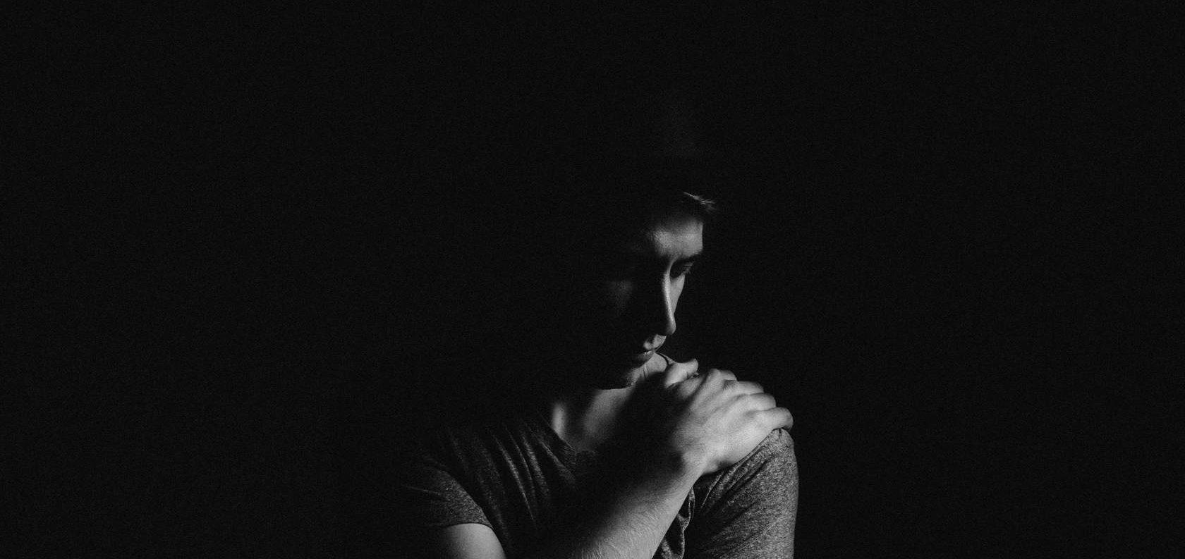 Man sitting alone in the dark, looking forlorn