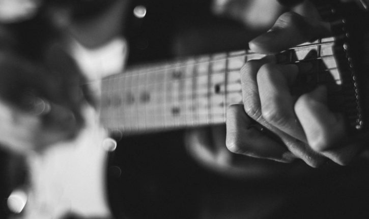 Close-up of hand on the fret board of a guitar