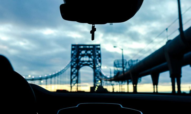 A view of a bridge through the windshield of a vehicle. A cross hangs from the rearview mirror.