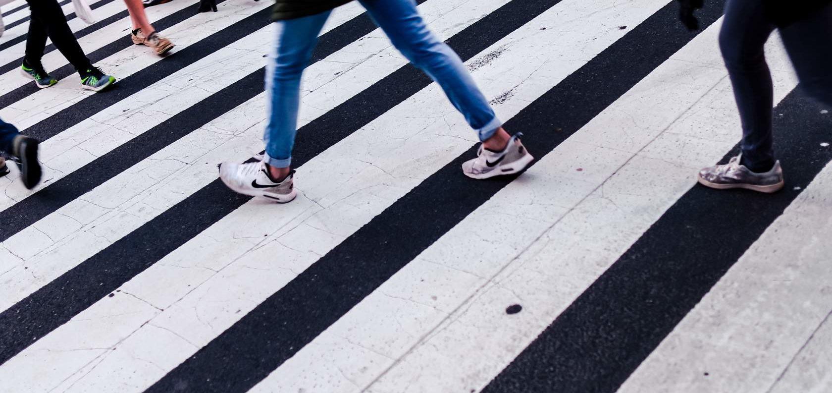 The feet of people walking through a crosswalk