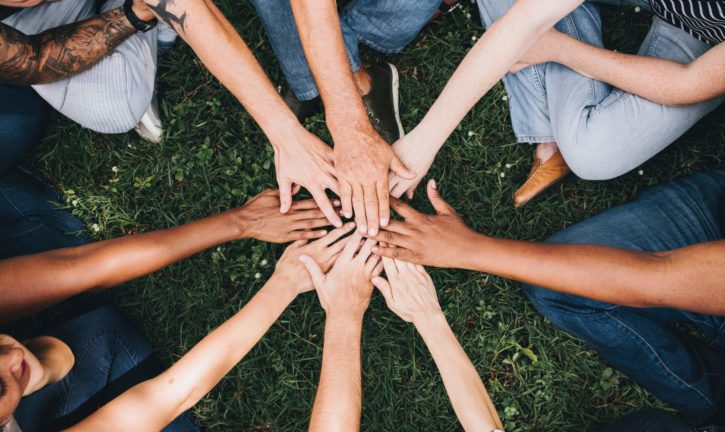 Eight people in a circle, each with a hand in the center