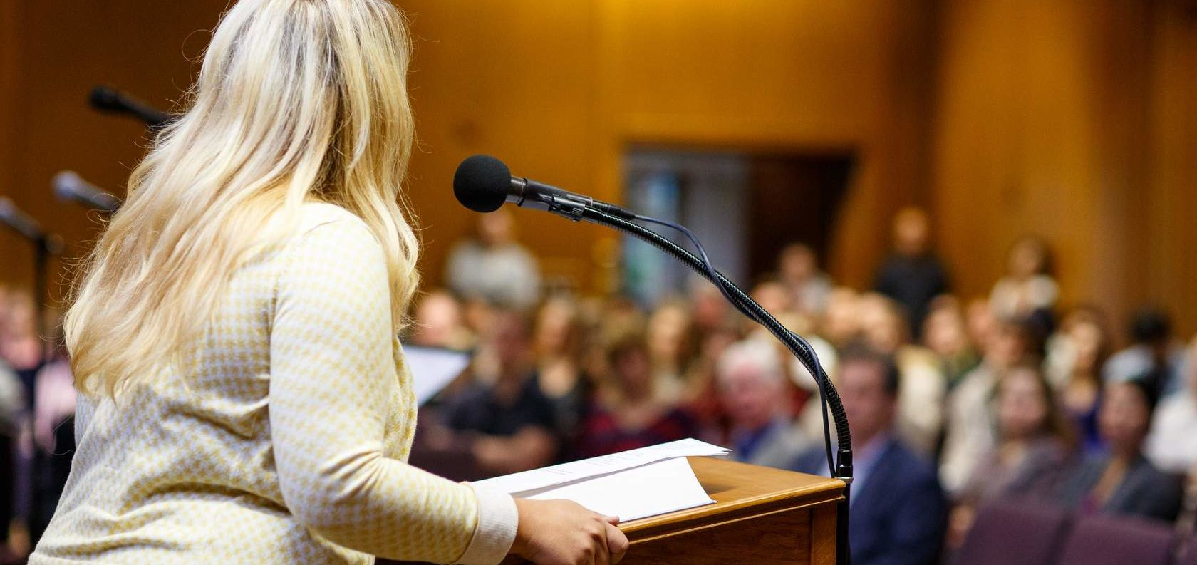A woman addresses a crowded room from a lectern