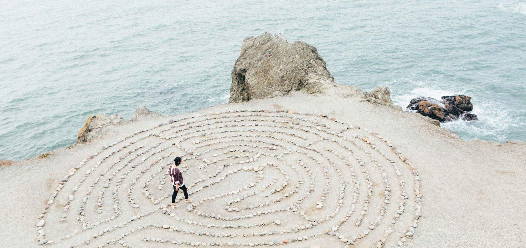 Person walking a labyrinth near the ocean