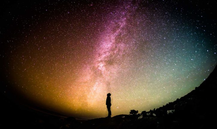 Person standing alone at night, looking up at a colorful night sky