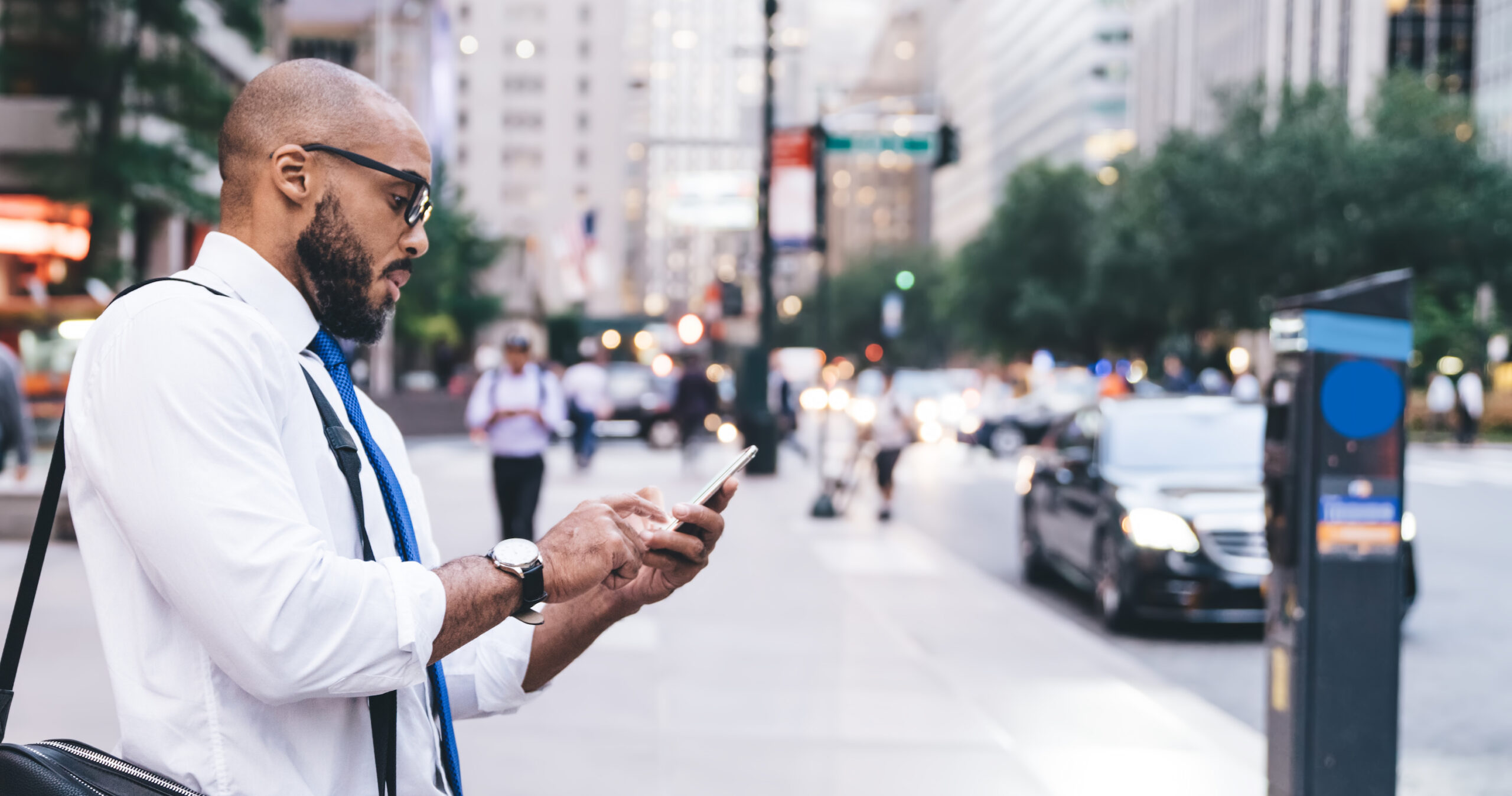 Side view of African American bald bearded office employee with bag looking at smartphone screen while standing on street of megapolis
